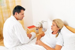 Ein Arzt bei Hausbesuch. Untersucht kranke Frau.